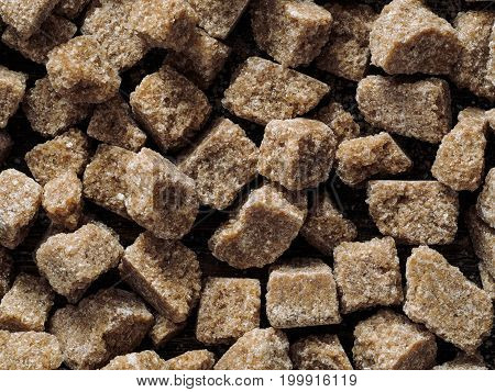 natural raw brown cane sugar cubes close up as background. Top view of brown sugar pattern.