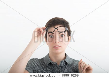 Young beautiful dark-haired woman in grey shirt with astonishment looks upwards against white studio background. Breaking news. Surprised pleasant woman holding his glasses on forehead.