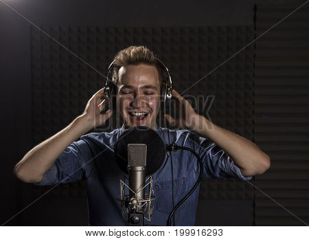 Music Passionate Singer and the Microphone. Young Caucasian Singer  Recording Album in the Professional Studio. Singing with Passion and positive
