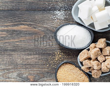 Top view of different types of sugar: natural raw brown and refined white cane sugar cubes, granulated brown and refined granulated white sugar in trendy plates on wooden table with copy space