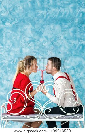 Young heterosexual couple photographed from behind while drinking water through a straw from one of a bottle on a bench. Happy couple drinking water. Studio shoot