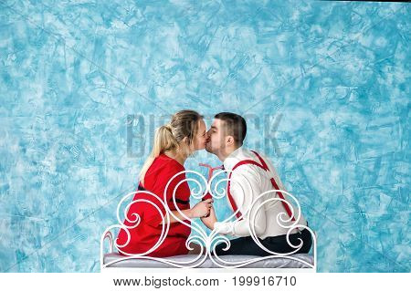 Young heterosexual couple photographed from behind while kissing and sitting on bench. Studio shoot