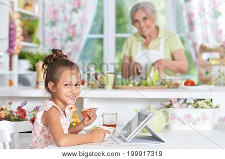 girl  using tablet with woman  cooking on background