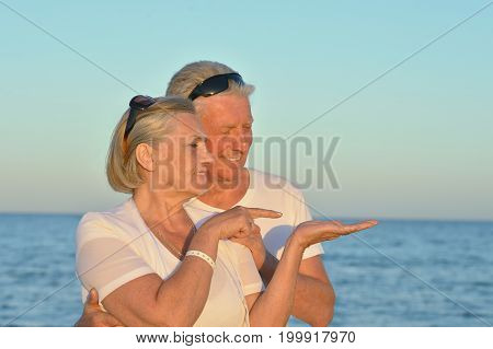 Happy senior couple standing together on seashore, woman pointing somewhere
