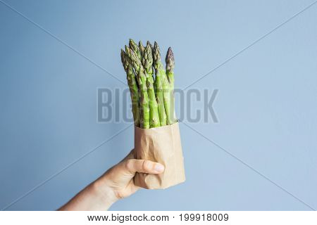Female hand holds Bundle of green asparagus on blue background. Concept of vegans, vegetarians and healthy food.