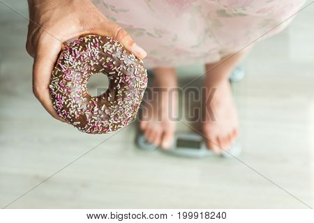 Diet Concept. Close-up of Woman's feet On Weighing Scale With Donut. Concept of Sweets, Unhealthy Junk Food and obesity