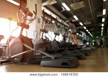Row of elliptical machines and treadmills in modern fitness center. Blurred background of Running people. Gym equipment.