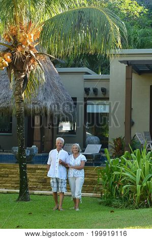 Portrait of a senior couple walking near hotel resort