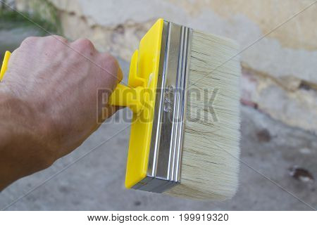 A man holds a wide new brush in his hands