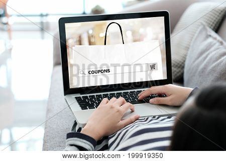 Woman hand searching coupon promotion on labtop computer screen background business and technology shopping online digital marketing concept