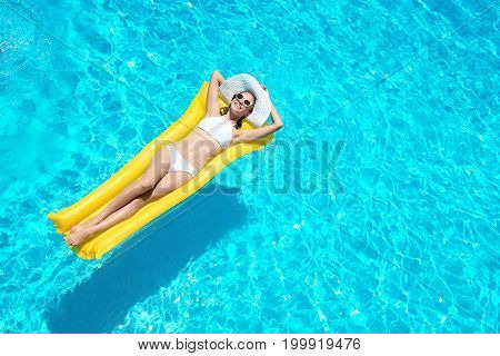 Beautiful young woman with inflatable mattress in blue swimming pool