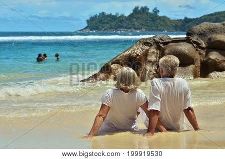 Happy elderly couple sitting  on  tropical beach