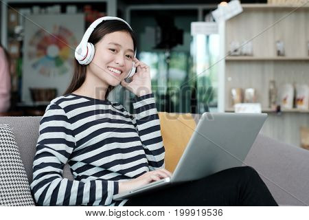 Young office woman wearing wireless headphones relaxing while working with laptop computer casual lifestyles people and technology