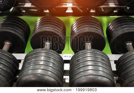 Closeup of dumbbell weights in modern fitness center. Gym equipment background.