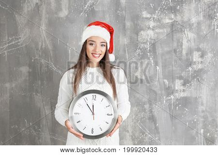 Young woman in Santa hat with clock on grunge background. Christmas countdown concept