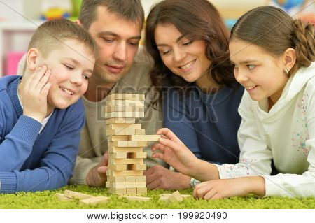 Happy parents and children playing with wooden blocks