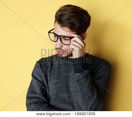 Young handsome man with great smile wearing fashion eyeglasses against  yellow background