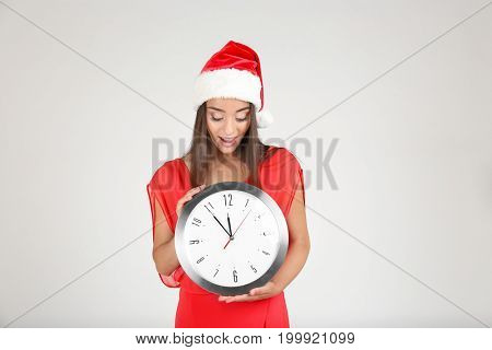 Young woman in Santa hat with clock on light background. Christmas countdown concept