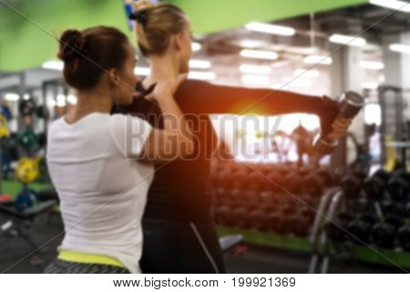 Gym background. Blurred picture of female exercising with weights with assistance of personal coach in modern fitness center.