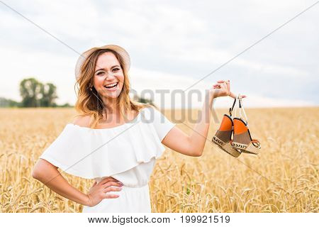 Woman holding shoe. Women loves shoes concept. Young woman holding a shoe - sale, consumerism and people concept