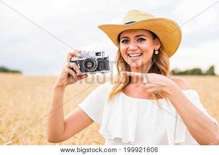 Woman holding retro camera in the field
