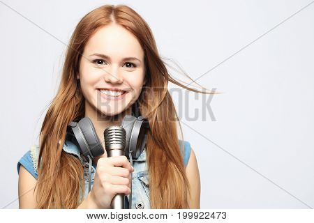 girl with microphone sings over white background