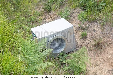washing machine abandoned in nature symbol of ecology and pollution against the environment