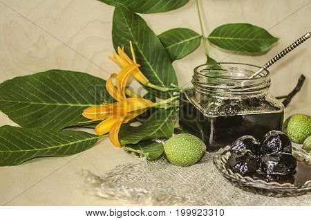 Walnut leaves and orange lilies on the table with glass jar with jam of green nuts