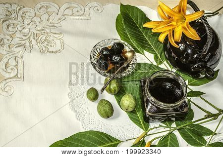 Porcelain teapot with a glass jar with jam of nuts on leaves with orange lilies on an embroidered tablecloth