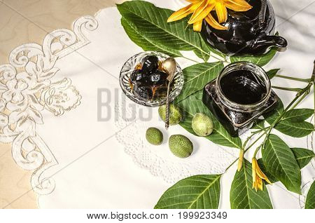 Walnut jam in a glass jar with a black porcelain teapot with orange lilies on walnut twigs lying on an embroidered tablecloth