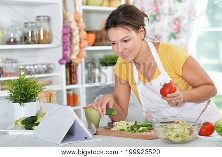 Beautiful young woman in headphones preparing dinner on kitchen
