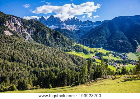 Val de Funes valley, Dolomites. Lovely sunny warm autumn day. Odle mountain peaks and forested mountains surrounded by green Alpine meadows