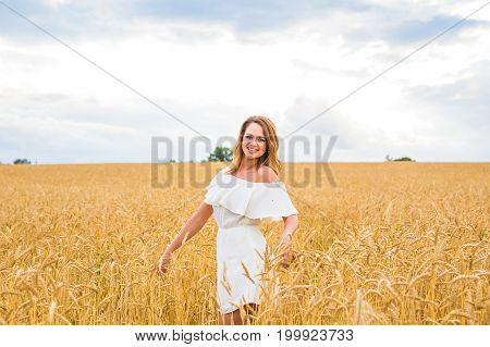 happiness, nature, summer, autumn, vacation and people concept - young woman in the field