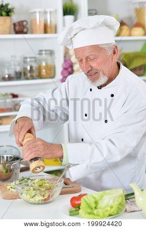 Senior male chef preparing dinner in kitchen