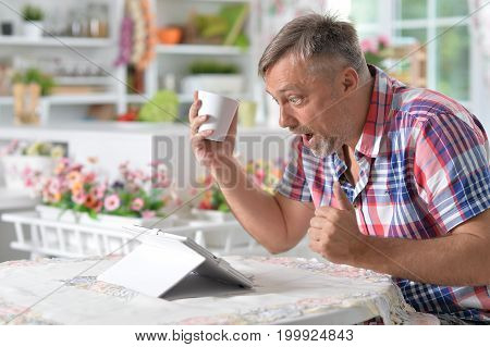 handsome mature man sitting at table with tablet