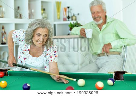 Portrait of smiling senior couple playing billiard together