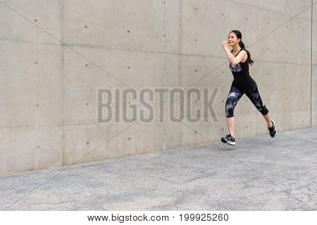 Young Female Jogger Jogging On Gray Background