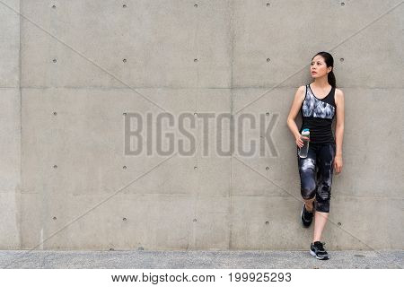 Seriously Fitness Woman Standing On Gray Wall