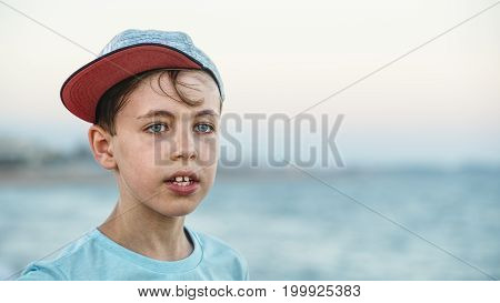Young blue eyed boy wearing a cap and looking in the distance