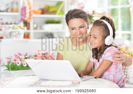 Mother and daughter sitting at table and using laptop