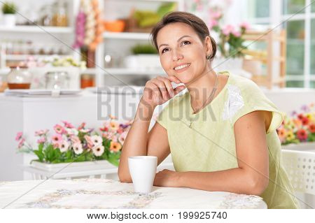 Beautiful young woman sitting at kitchen table with cup of tea