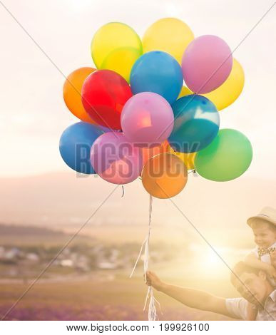 Father and son playing with balloons on lavender field at the sunset time. People having fun on the field. Concept of friendly family and of summer vacation.