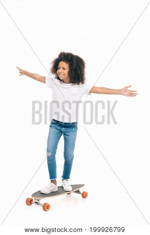 happy african american girl with open arms standing on skateboard isolated on white
