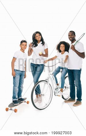 happy african american family with sport equipment smiling at camera isolated on white