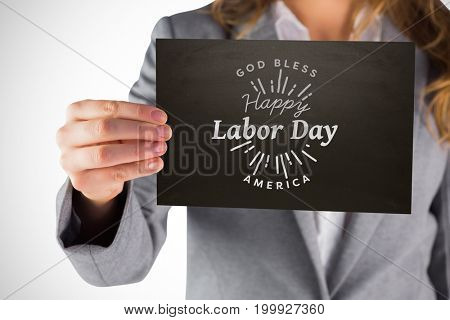 Businesswoman showing card against digital composite image of happy labor day and god bless america text