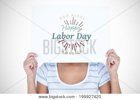 Woman holding blank sign in front of face against digital composite image of happy labor day and god bless america text