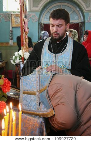 VOYUTYN UKRAINE - 14 October 2008: Priest covered robe head of woman during confession in church