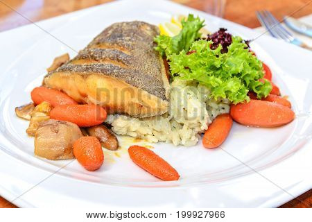 Delicious fried fish Halibut served sweet with carrots pear rice lettuce and lemon.