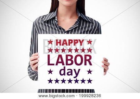 Pretty woman holding a white sheet of paper against poster of happy labor day text
