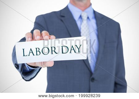 Midsection of businessman holding blank card against labor day text